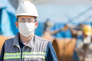 Man wearing safety helmet and mask in front of safety workers